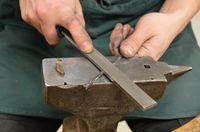Passage de la lime sur le ressort pour enlever les aspérités d'acier du ressort